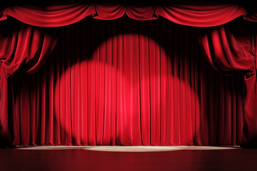 Theater Stage With Red Velvet Curtains And Spotlights.