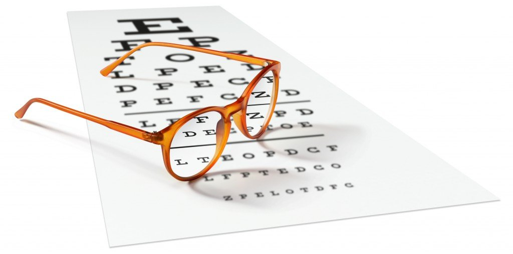 Orange Eyeglasses On Visual Test Chart Isolated On White. Eyesight Concept