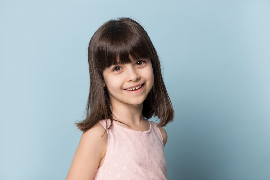 Close Up Of Smiling Little Girl Posing In Studio