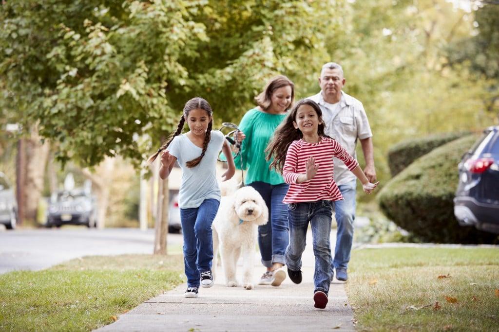 Grandparents And Granddaughters Walking Dog Along Street