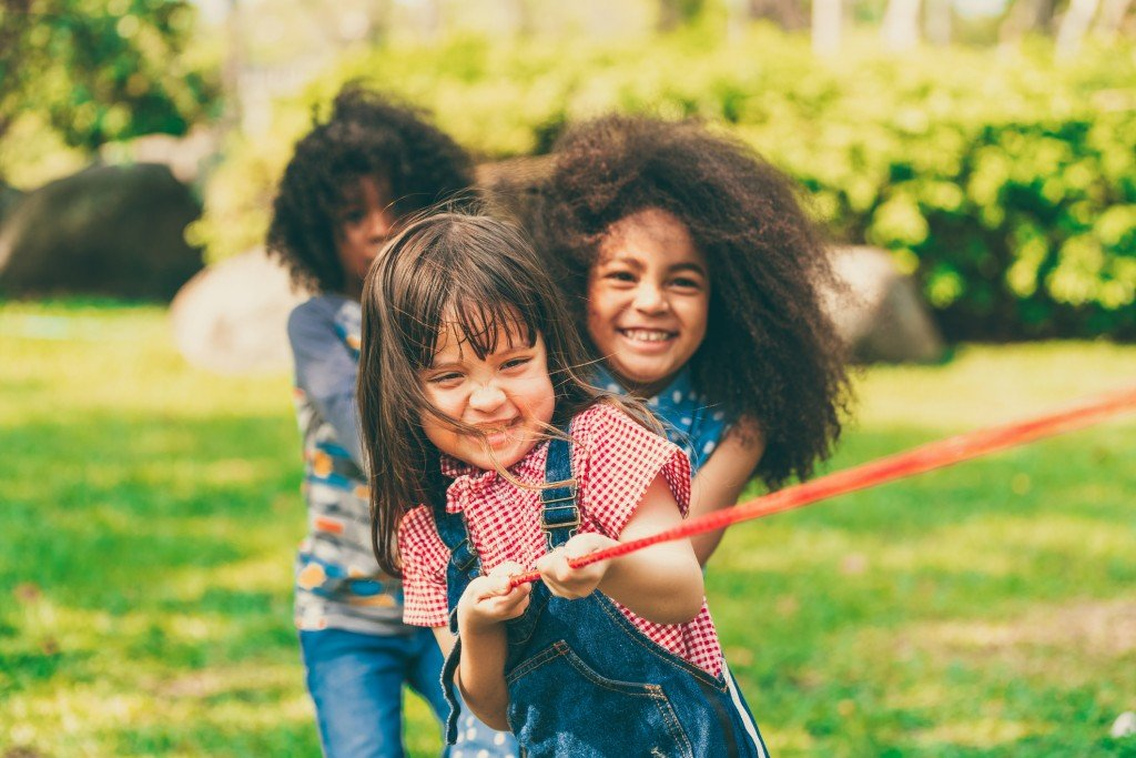 Happy Children Playing Tug Of War And Having Fun During Summer Camping In The Park.