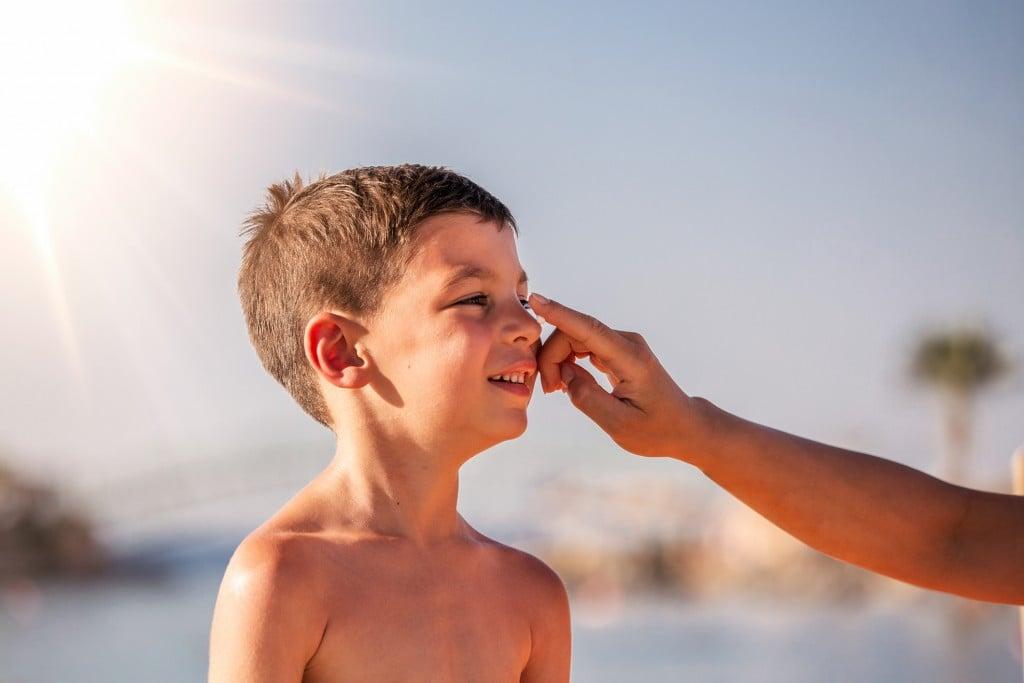 Mother Applying Sunblock Cream On Son Face. Mother Put Sunblock Cream On Little Boy Face At Beach