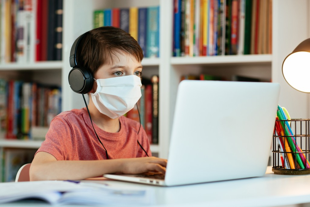 Child Wearing Face Mask Learning At Home.