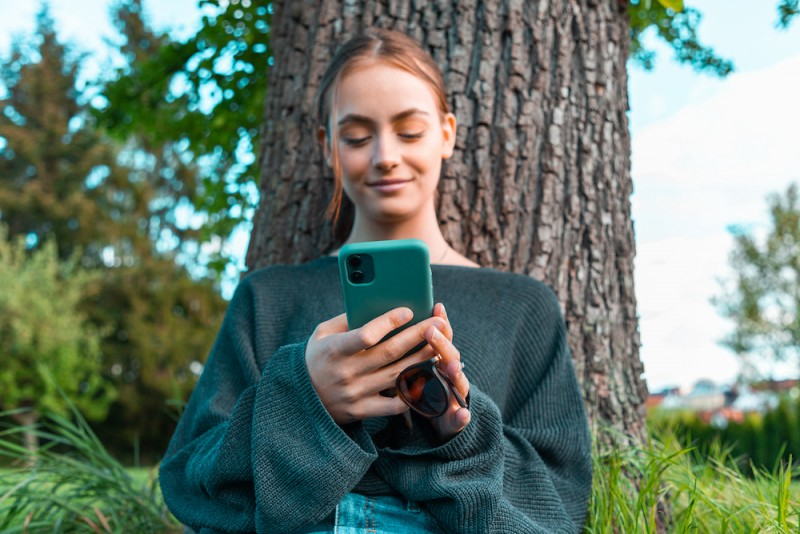 Confident Smile. Young Woman On Mobile Phone