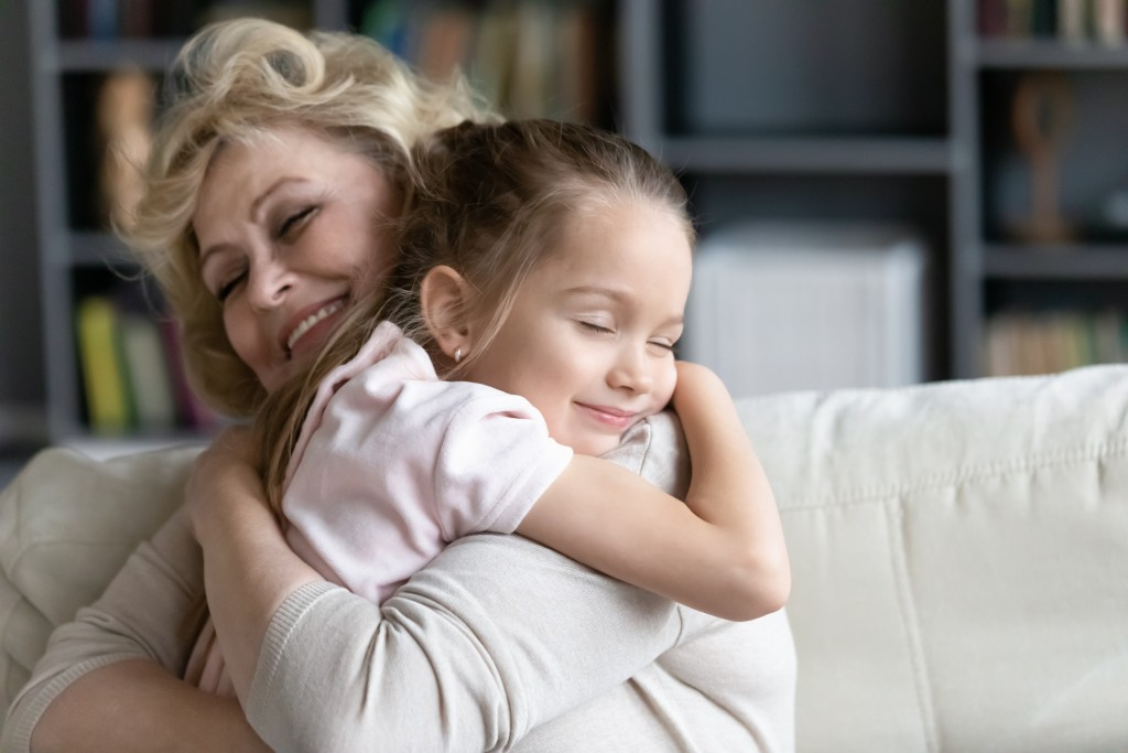 Happy Senior Granny Cuddle With Cute Preschooler Granddaughter