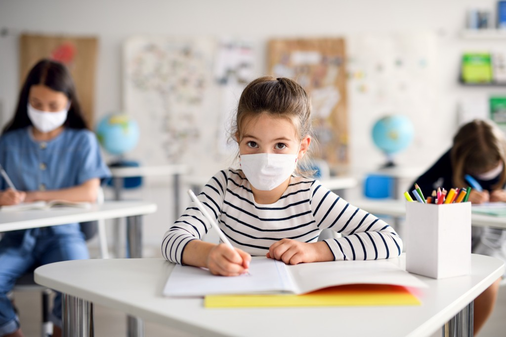 Child With Face Mask Back At School After Covid 19 Quarantine And Lockdown, Writing.