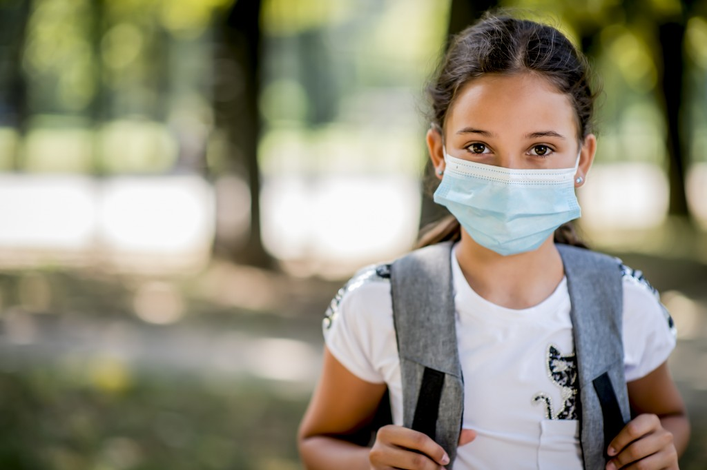 Portrait Of Girl Going To School With Protective Face Mask On.