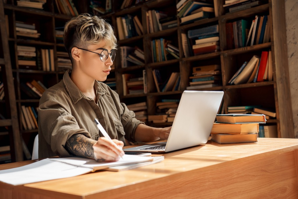 Young Adult Student Girl Working On Laptop In Library