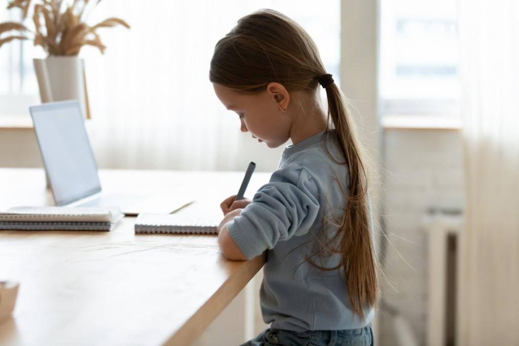 Focused Small Adorable Caucasian Girl Preparing Homework Alone.
