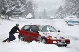 Alex Vlasity helps push out a passing car which became bogged on an unplowed road after a night of heavy snowfall, in Boulder, Colo., Tuesday, Dec. 15, 2015. The biggest winter storm to hit the Denver area so far this season has left most schools closed and created some havoc on the roads for those forced to commute. (AP Photo/Brennan Linsley)