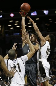 Davidson's Jack Gibbs (12) shoots over St. Bonaventure's Jaylen Adams (10) and Dion Wright (21) during the first half of an NCAA college basketball game during the Atlantic 10 men's tournament Friday, March 11, 2016, in New York.  (AP Photo/Frank Franklin II)
