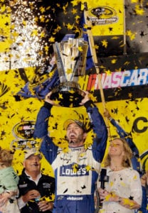 Jimmie Johnson lifts the trophy as he celebrates the NASCAR Sprint Cup auto race and series title, Sunday, Nov. 20, 2016, in Homestead, Fla. (AP Photo/Terry Renna)