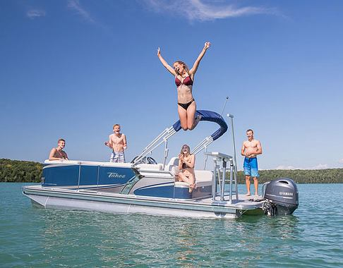 Girl in bikini jumping off of pontoon boat into the water