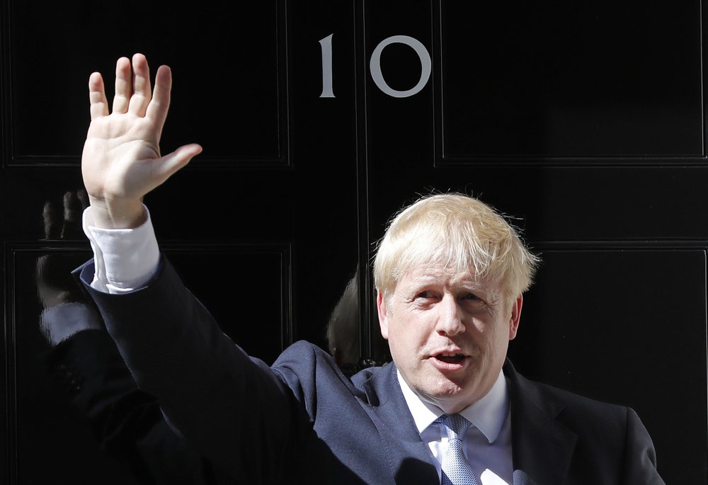 Britain's Prime Minister Boris Johnson waves from the steps outside 10 Downing Street in London