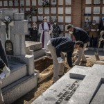 A Priest And Relatives Pray As A Victim Of The Covid 19 Is Buried By Undertakers At The Almudena Cemetery In Madrid, Spain, March 28, 2020