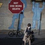 A Woman Wearing A Mask Crosses The Street In Front Of A Mural About Traffic Accidents Reading,