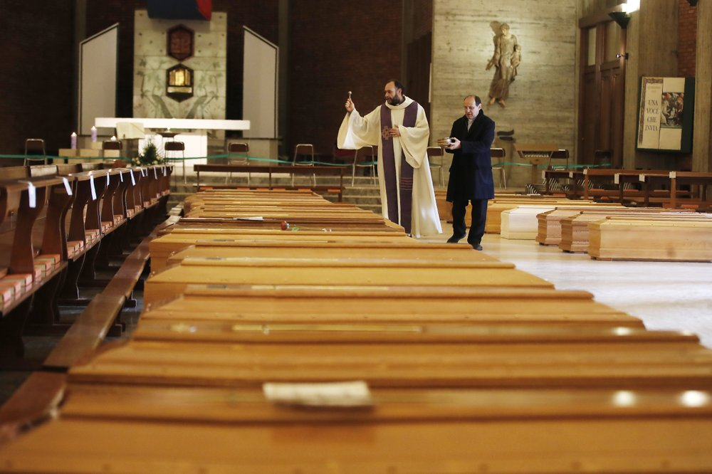 Don Marcello Crotti, Left, Blesses The Coffins With Don Mario Carminati In The San Giuseppe Church In Seriate, Italy, Saturday, March 28, 2020.