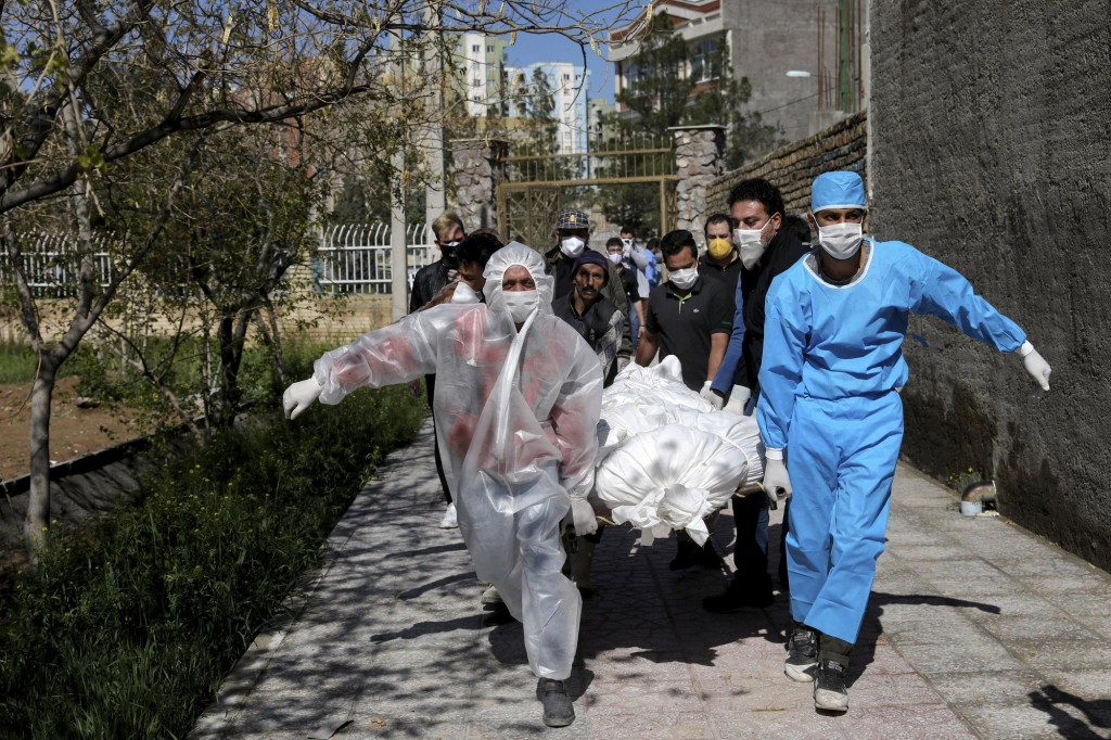 People Wearing Protective Clothing Carry The Body Of A Victim Who Died After Being Infected With The New Coronavirus At A Cemetery Just Outside Tehran, Iran, March 30, 2020.