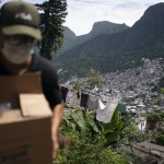 Local Volunteer Carries A Package With Soap And Detergent To Be Distributed In An Effort To Stop The Spread Of The New Coronavirus In The Rocinha Slum Of Rio De Janeiro, Brazil, March 24, 2020