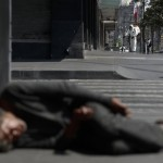 A City Worker Sprays Disinfectant As A Man Sleeps On The Street, In Central Mexico City