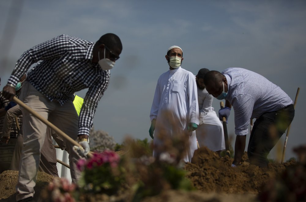 Mourners Shovel Dirt Onto The Grave Of A Guinean Man, Who Died Of Covid 19