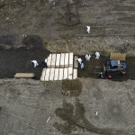 Workers Bury Bodies In A Trench On Hart Island, April 9, 2020, In The Bronx Borough Of New York