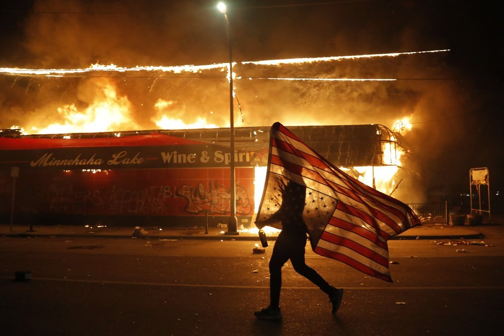 A Protester Carries A U.s. Flag Upside, A Sign Of Distress, Next To A Burning Building Thursday, May 28