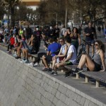 People Sit As Others Exercising In A Seafront Promenade In This Photo Taken With A Telephoto Lens In Barcelona, Spain