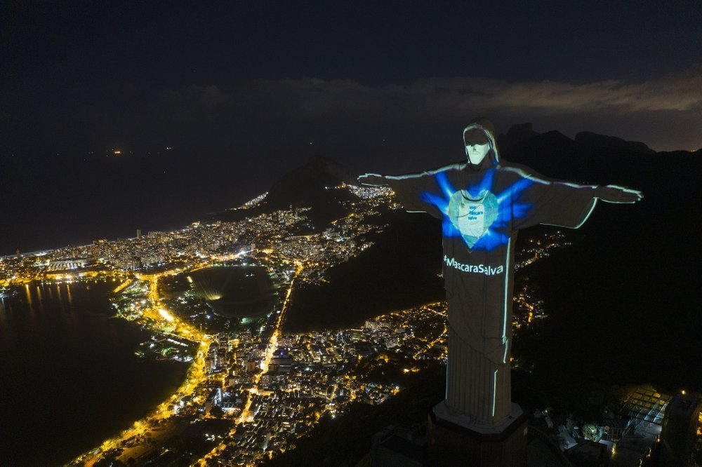 "The Iconic Christ The Redeemer Statue Is Lit Up As If Wearing A Protective Mask And With A Hashtag That Reads In Portuguese ""mask Saves,"" Amid The New Coronavirus Pandemic, In Rio De Janeiro, Brazil"