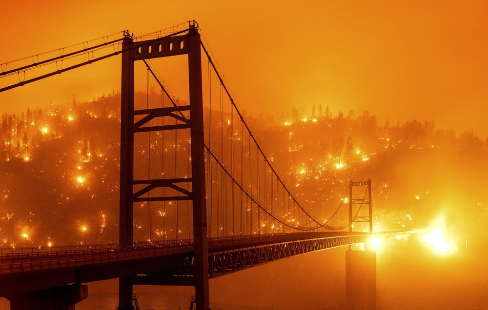 In This Image Taken With A Slow Shutter Speed, Embers Light Up A Hillside Behind The Bidwell Bar Bridge As The Bear Fire Burns In Oroville, Calif