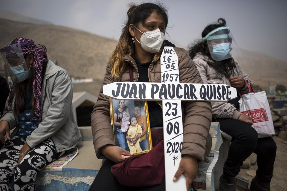 Ruth Morales, 36, Center, Waits For The Arrival Of The Coffin Of Her Husband, Juan Paucar Quispe, 63, Who Died From Covid 19 Complications, During His Burial At A Cemetery In Carabayllo, Lima, Peru