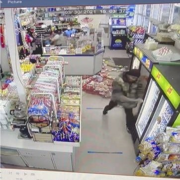 man with a pole trashing an Asian-owned convenience store