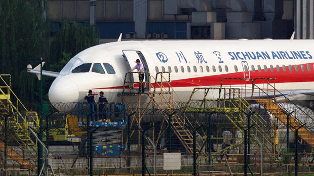 Workers inspect a Sichuan Airlines aircraft that made an emergency landing after a windshield on the cockpit broke off