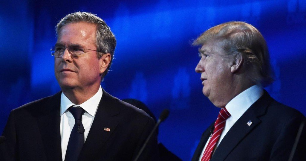 Republican Presidential hopefuls Donald Trump (R) and Jeb Bush look on during a break in the CNBC Republican Presidential Debate