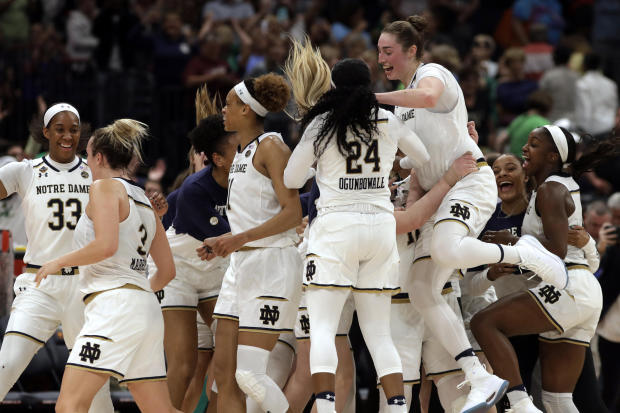 The Notre Dame team celebrates at the end of the team's 81-76 win over Connecticut during a Final Four semifinal of the NCAA women's college basketball tournament Friday