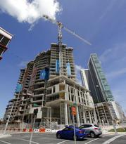 A high-rise building under construction is shown next to a high-rise condominium building