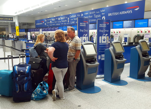 Passengers stand at the British Airways check-in desk after the airport suffered an IT systems failure