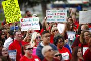 Teachers hold placards during a rally outside the state Capitol