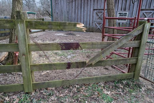A fence is broken and marked with blood after a llama tried to escape an attack by an unknown group of canines on a 16-acre farm that is situated near the Louisville Zoo and I-264 in a suburban area. Source: Courier Journal