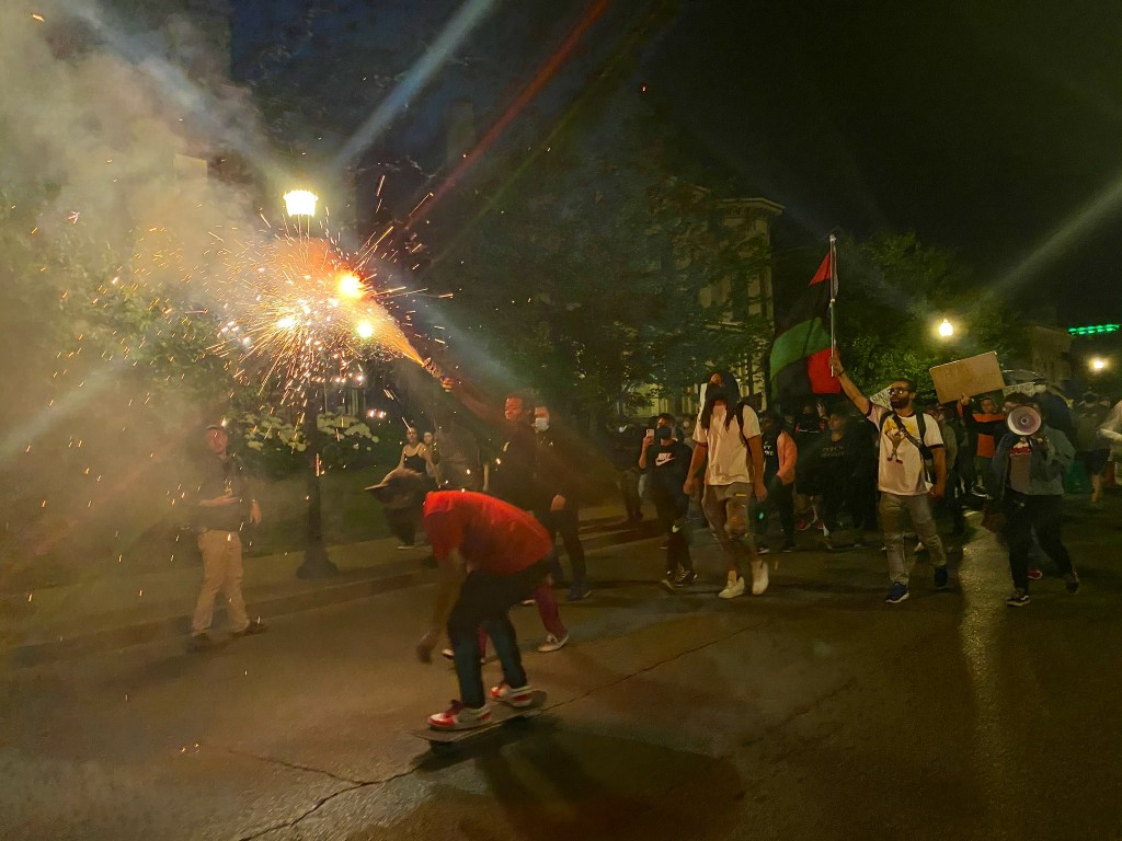 Protesters light fireworks during Sunday