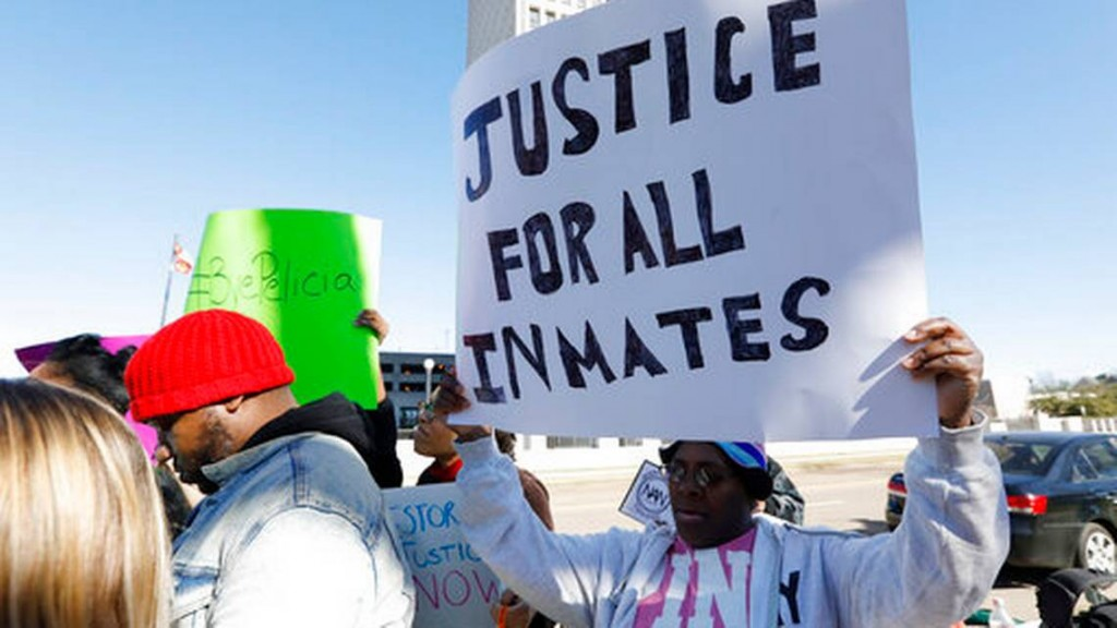 Prisoner advocates hold signs supporting inmate rights at a protest outside the Capitol in Jackson