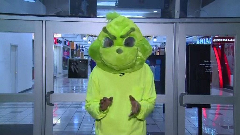 Person dressed as Grinch throws cash in mall