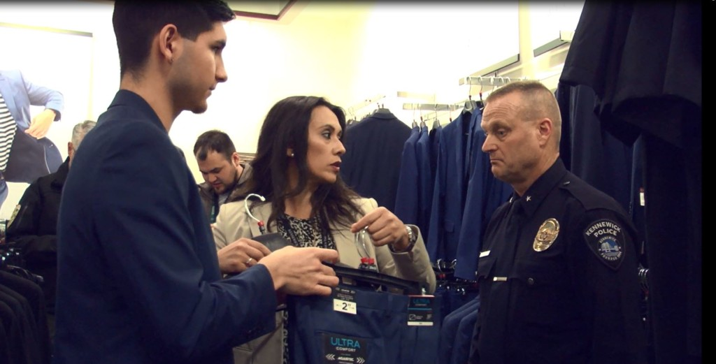 Teen getting help shopping for his suit from an officer and a lady