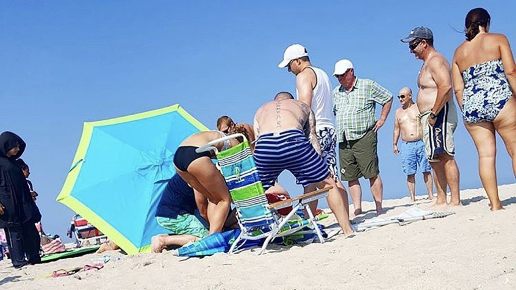 Winds lift beach umbrella, launching it through a tourist's ankle