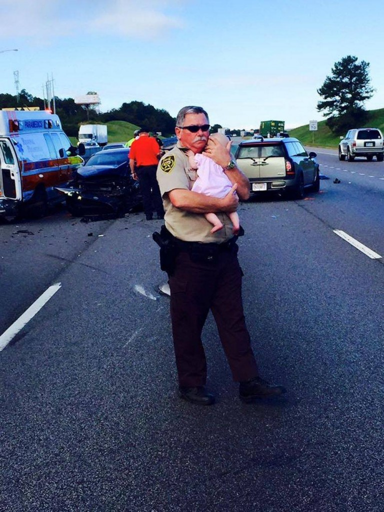 Deputy comforts baby at the scene of Alabama crash