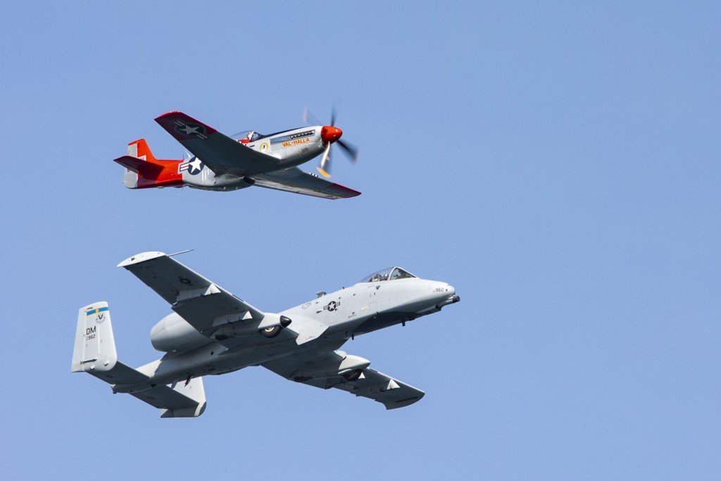 U.S. Air Force A-10C Thunderbolt II and a P-51 flying formation during the airshow.