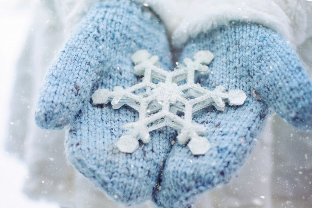stock image of blue mittens holding a massive snowflake