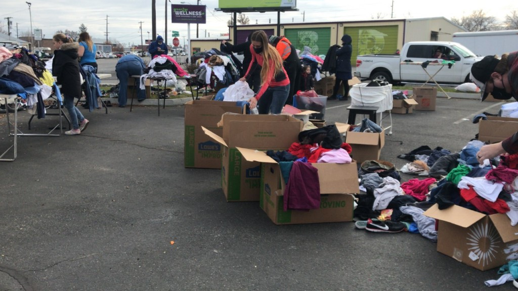 People gather to look through free items at a parking lot in Kennewick