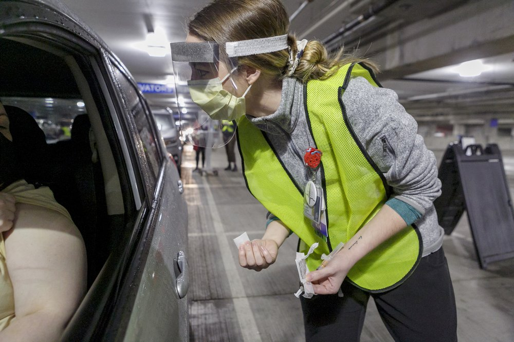 FILE - In this Jan. 10, 2021, file photo Nurse Madison Freenling prepares to administer a Moderna COVID-19 vaccine at a drive-thru vaccination clinic in Portland, Ore. Oregon health officials say they are expecting chaos next week, when about 167,000 people who are 80 years or older will become eligible for the COVID-19 vaccine. In preparation, Gov. Kate Brown announced Friday, Feb. 5, that additional National Guard members will be deployed to help with the state's 211 system, to field calls and texts from seniors signing up and seeking information on vaccinations. (Kristyna Wentz-Graff/Pool Photo via AP, File)