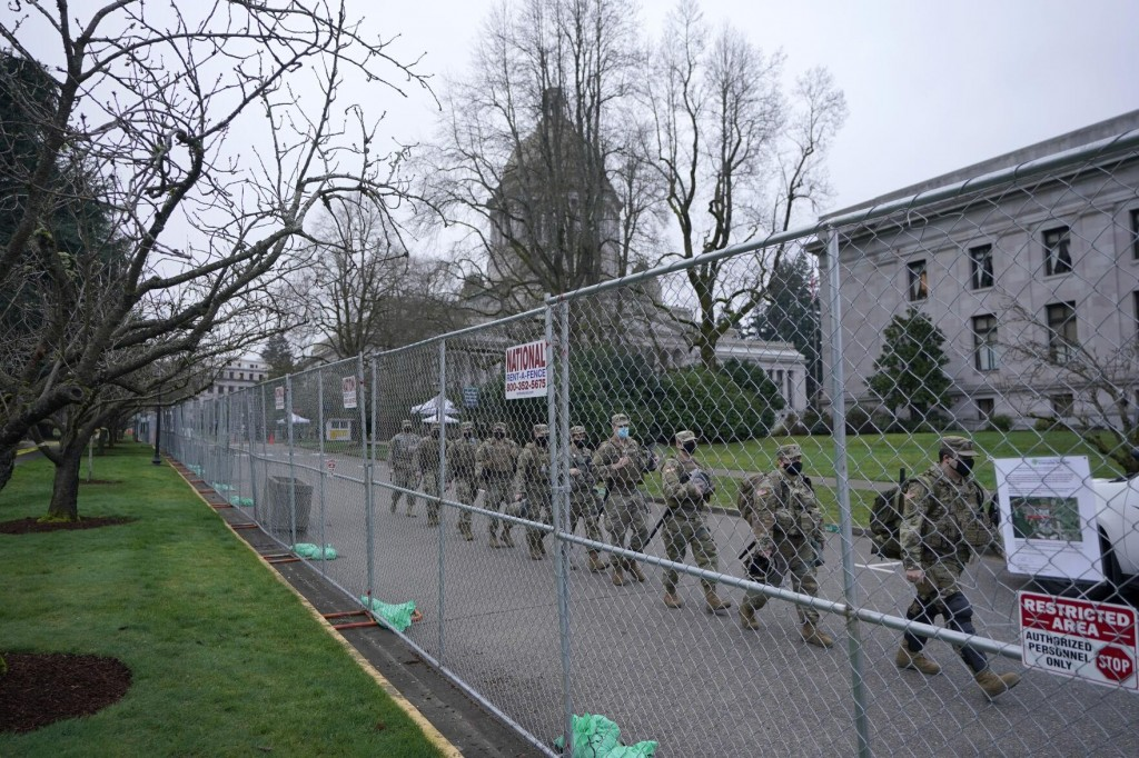 Washington National Guard members walk in formation along a perimeter fence near the Legislative Building, Wednesday, Jan. 20, 2021, at the Capitol in Olympia, Wash. Members of the Guard and Washington State Patrol troopers have been in place all week on the campus providing security against possible protests connected with the inauguration of President Joe Biden and the departure of former President Donald Trump in Washington, D.C.